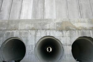 A Palestinian walks through a water pipe underneath the controversial Israeli barrier in al-Ram, on the edge of Jerusalem. Credit: Reuters