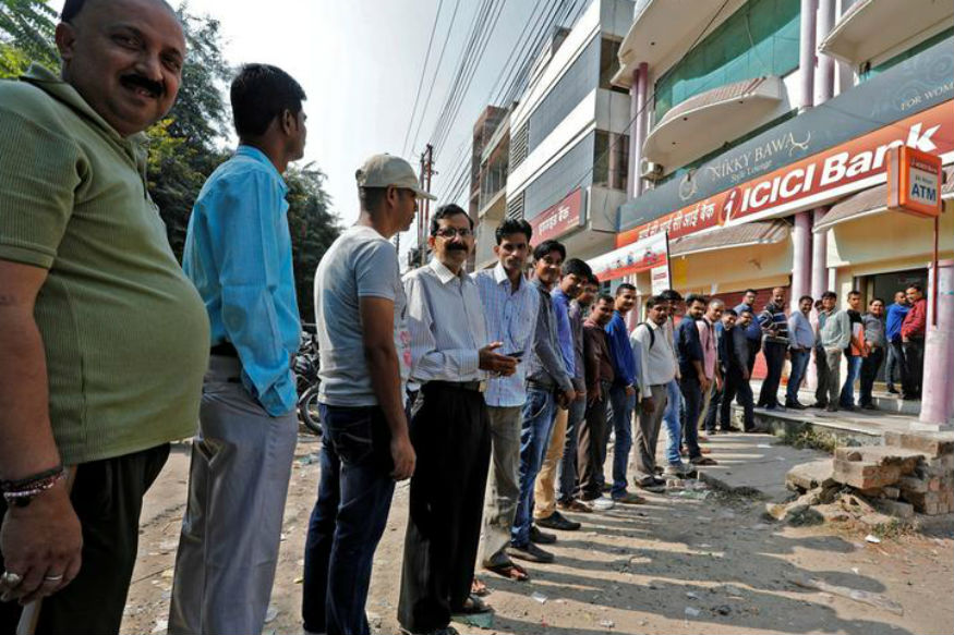 People stand in lines outside an ATM. Credit: Reuters