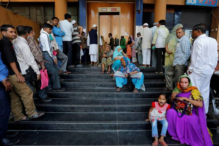 People wait for a bank to open in Ahmedabad, India. Credit: Amit Dave/Reuters