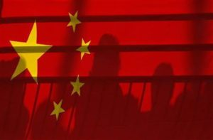 The shadows of spectators are seen through a Chinese national flag during the men's kayak (K1) semifinal at the Beijing 2008 Olympic Games August 12, 2008. Credit: Reuters/Phil Noble