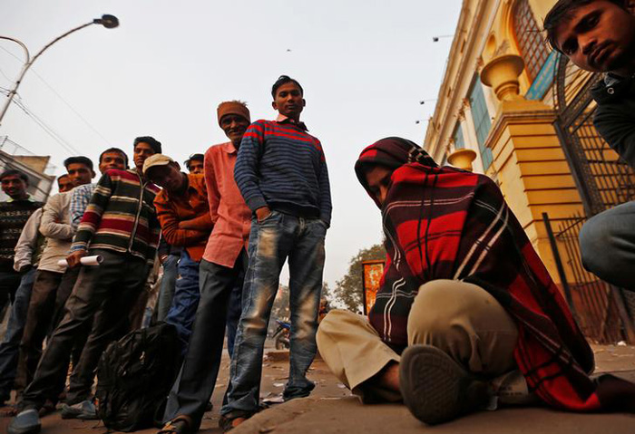 A man wrapped in a quilt sleeps as others stand in a queue outside a bank to exchange their old high-denomination banknotes in the early hours, in the old quarters of Delhi. Credit: Reuters/Adnan Abidi/Files