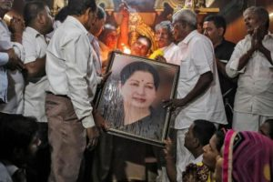 Well wishers of Tamil Nadu Chief Minister Jayalalithaa Jayaraman hold her portrait as they pray at a temple in Mumbai. Credit: Reuters