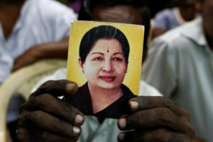 A supporter of J. Jayalalithaa holds her photo at the AIADMK party office in Mumbai, India, December 5, 2016. Credit: Reuters/Danish Siddiqui