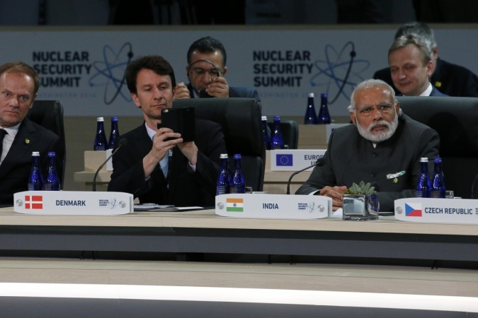 A member of Denmark's delegation (C) takes a picture with his phone while seated next to India's Prime Minister Narenda Modi (R) at the start of the second plenary session of the Nuclear Security Summit in Washington April 1, 2016. Credit: Reuters