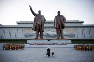 A woman and her daughter their respects at statues of North Korea founder Kim Il Sung (L) and late leader Kim Jong Il in Pyongyang October 11, 2015. Credit: Reuters/Damir Sagolj/File Photo