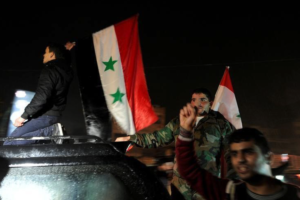 Supporters of Syria's President Bashar al-Assad carry their national flags as they celebrate what they say is the Syrian army's victory against the rebels, in Aleppo, Syria December 12, 2016. Credit:Reuters/Omar Sanadiki