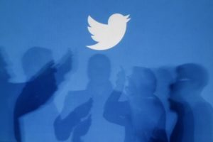 The shadows of people holding mobile phones are cast onto a backdrop projected with the Twitter logo in this illustration picture taken in Warsaw September 27, 2013. Credit: Reuters/Kacper Pempel