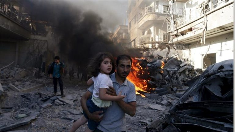 A man carries a girl as they rush away from a site hit by an air strike Credit: Bassam Khabieh/Reuters/Files
