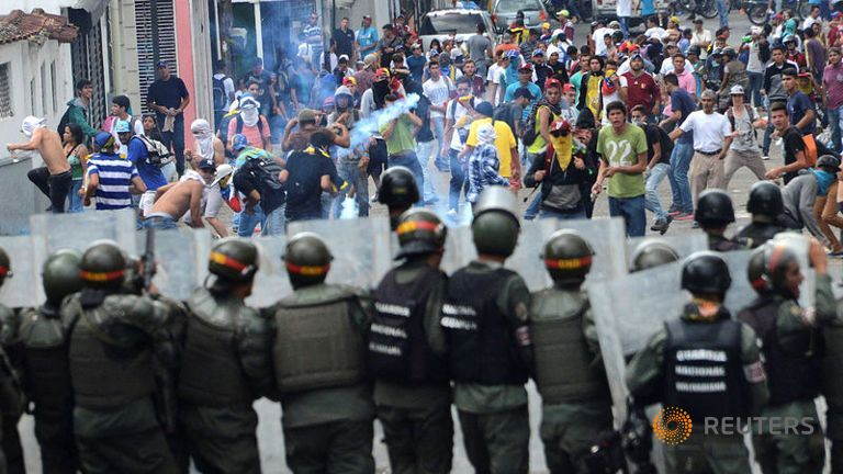 Demonstrators clash with members of the Venezuelan National Guard. Credit: Reuters