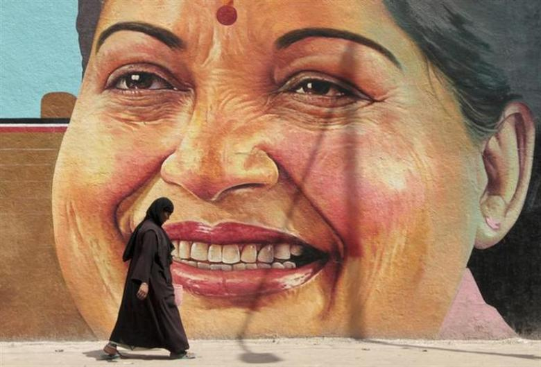 A woman walks past a portrait of J. Jayalalithaa, chief minister of Tamil Nadu, in Chennai March 13, 2012. Credit: Reuters/Babu