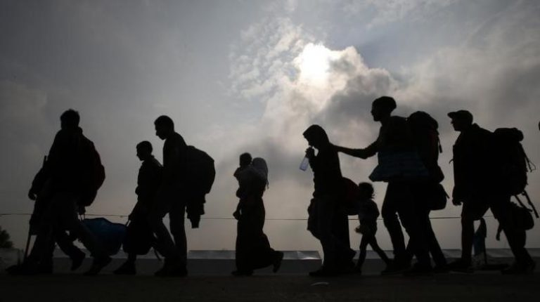 Migrants are silhouetted against the sky as they make their way to board buses in Nickelsdorf, Austria, October 6, 2015. Credit: Leonhard Foeger/Reutes/Files