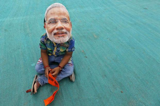 A boy wearing a Narendra Modi mask sits as he waits for the start of an election campaign rally being addressed by Modi in Kheralu town in Gujarat. Credit: Amit Dave/Reuters/Files