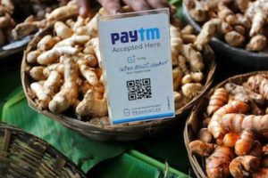 An advertisement board displaying a QR code for Paytm, a digital wallet company, is seen placed amidst vegetables at a roadside vendor's stall in Mumbai, India, November 19, 2016. REUTERS/Shailesh Andrade