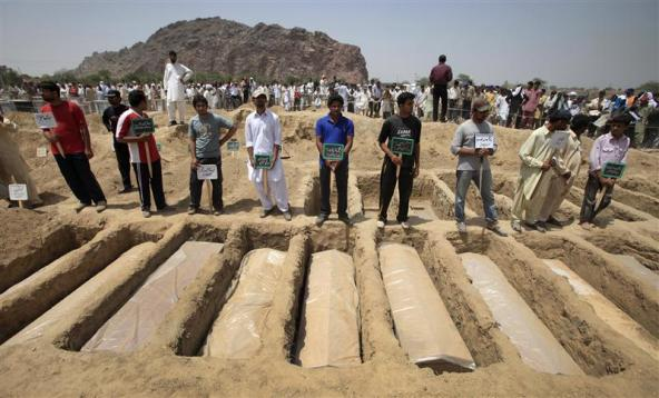 Ahmadis stand over graves of victims of an attack on one of their mosques, in Rabwah, May 29, 2010. Credit: Reuters/Files