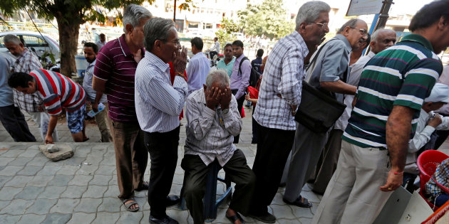 A man sits in a queue to deposit or exchange his old high denomination banknotes outside a bank in Ahmedabad, India November 21, 2016. Credit: Amit Dave/Reuters/Files