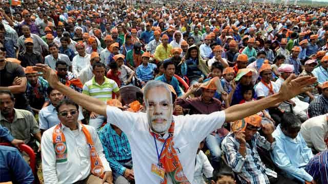 A man wearing a Narendra Modi mask. Credit: PTI