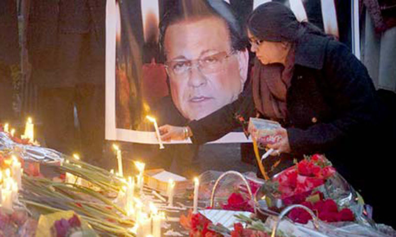 A women lighting a candle at the death anniversary of Salman Taseer. Credit: Reuters
