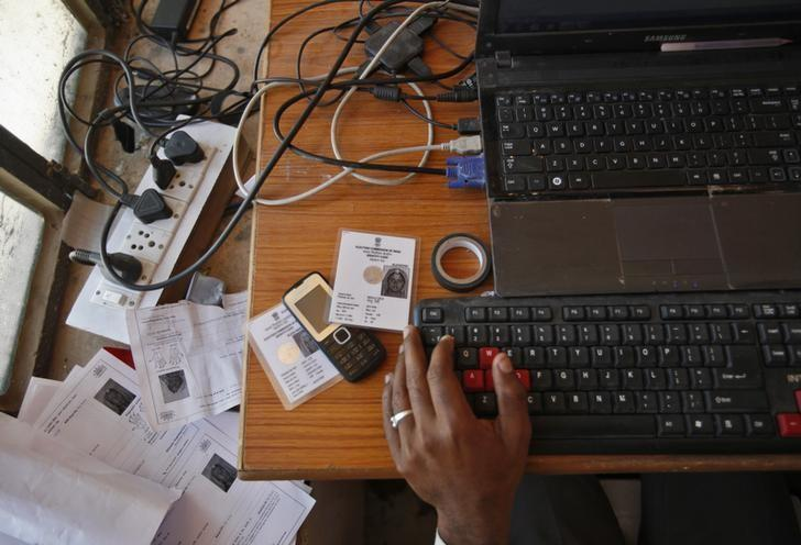 An operator works on his table while enrolling villagers for Aadhaar in Rajasthan. Credit: Reuters