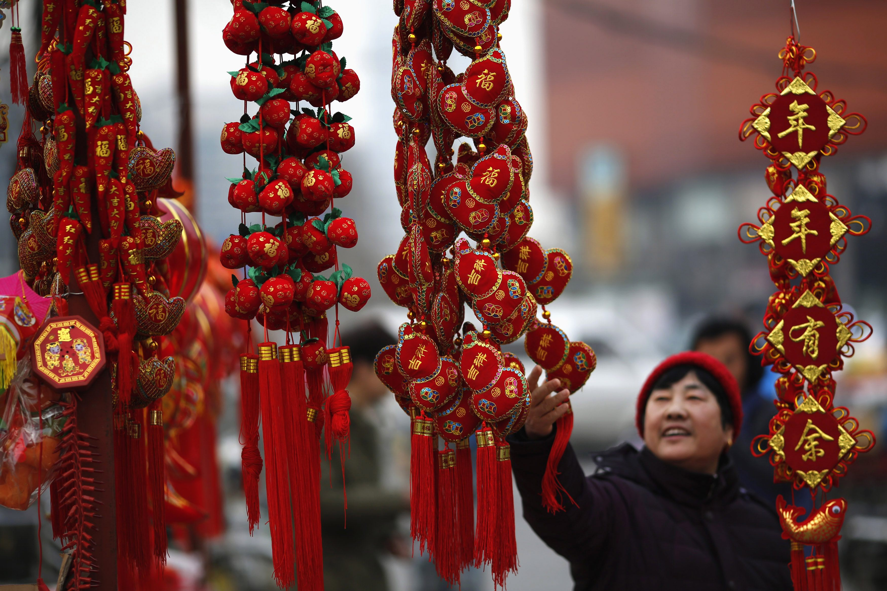 A woman looks at traditional decorations celebrating for the upcoming Chinese Lunar New Year at a market in Beijing February 6, 2015. Credit: Reuters/Kim Kyung-Hoon