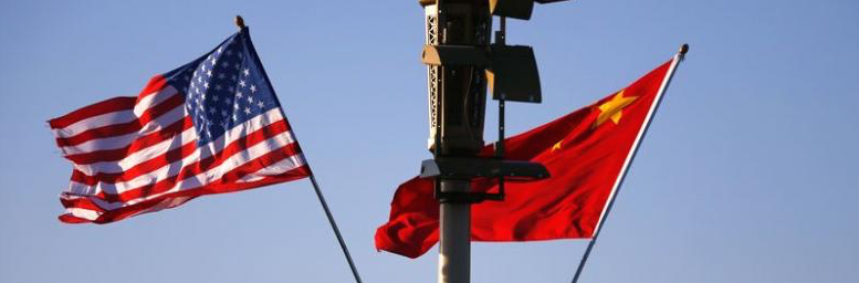 US (L) and Chinese national flags flutter on a light post at the Tiananmen Square. Credit: Reuters/Petar Kujundzic