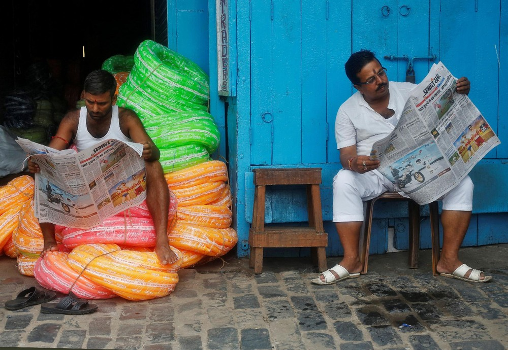 Men reading newspapers. Credit: Reuters
