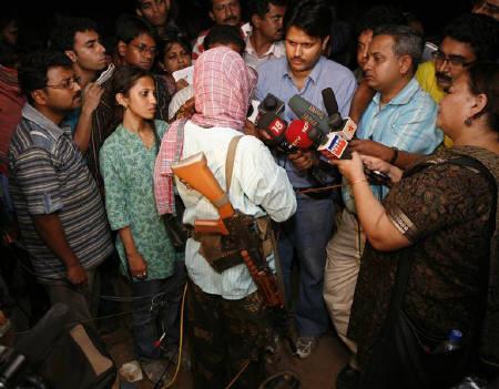 Maoist leader Kishenji (C, facing back) speaks to the media in Bholagara village of West Bengal October 22, 2009. Credit: Reuters/Jayanta Shaw/Files