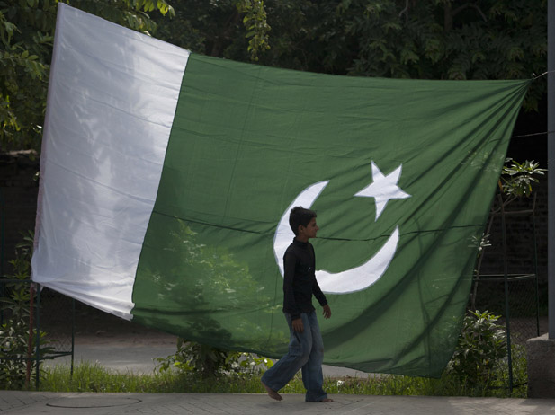 A boy walks past a Pakistani flag along a road in Rawalpindi. Credit: Reuters/Faisal Mahmood/Files
