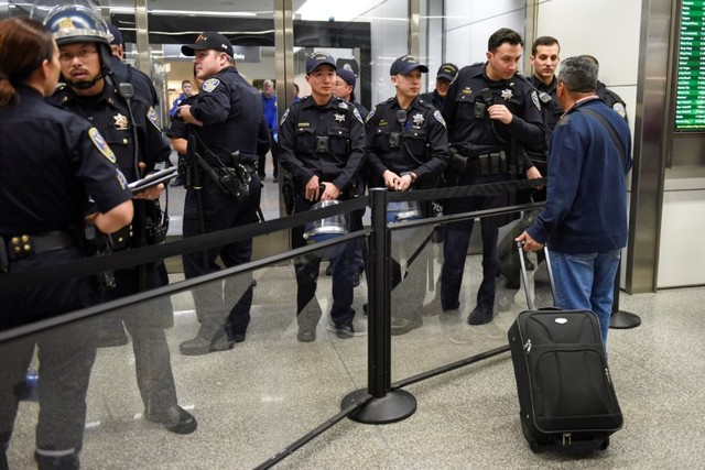Police redirect travelers after the security check point was closed due to protests in Terminal 4 at San Francisco International Airport in San Francisco, California, US, January 28, 2017. Credit: Reuters/Kate Munsch