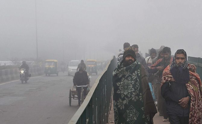 New Delhi: File photo of people wrapped in woolens during a cold wave i n Delhi. Credit : PTI