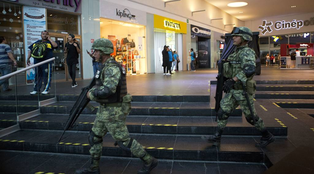 Soldiers walk inside Plaza Las Americas mall following reports of gunfire in Cancun, Mexico, Tuesday, Jan. 17, 2017. Gunmen attacked the state prosecutor's office in this Caribbean resort city Tuesday, ratcheting up tensions just a day after a deadly shooting at a music festival in a nearby town. Credit: AP/Rebecca Blackwell