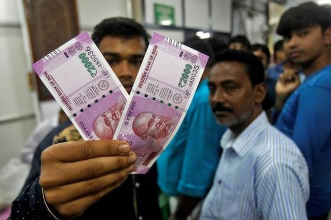 A man displays the new 2000 Indian rupee banknotes after withdrawing them from State Bank of India in Agartala. Credit: Reuters/Files