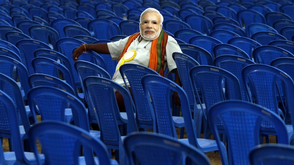 A man sits wearing a Narendra Modi mask before an event. Credit: Reuters/Files