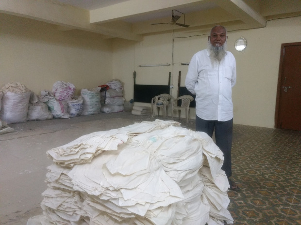 Mannan Siddiqui with gray fabric produced in his factory. Courtesy: IndiaSpend