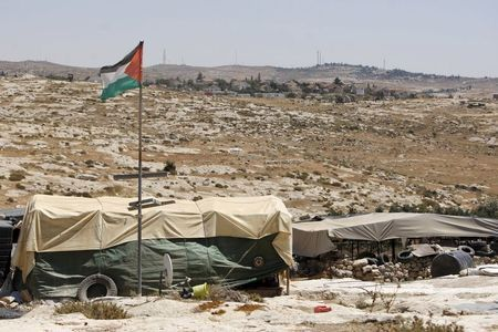 A Palestinian flag and tents in Susya village, south of the West Bank city of Hebron. Credit: Reuters/Mussa Qawasma
