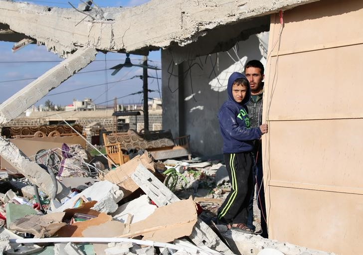 Civilians stand in a damaged house after an airstrike in the rebel-held southern town of Bosra al-Sham, Deraa Governorate, Syria February 17, 2017. Credit: Reuters/Alaa Al-Faqir