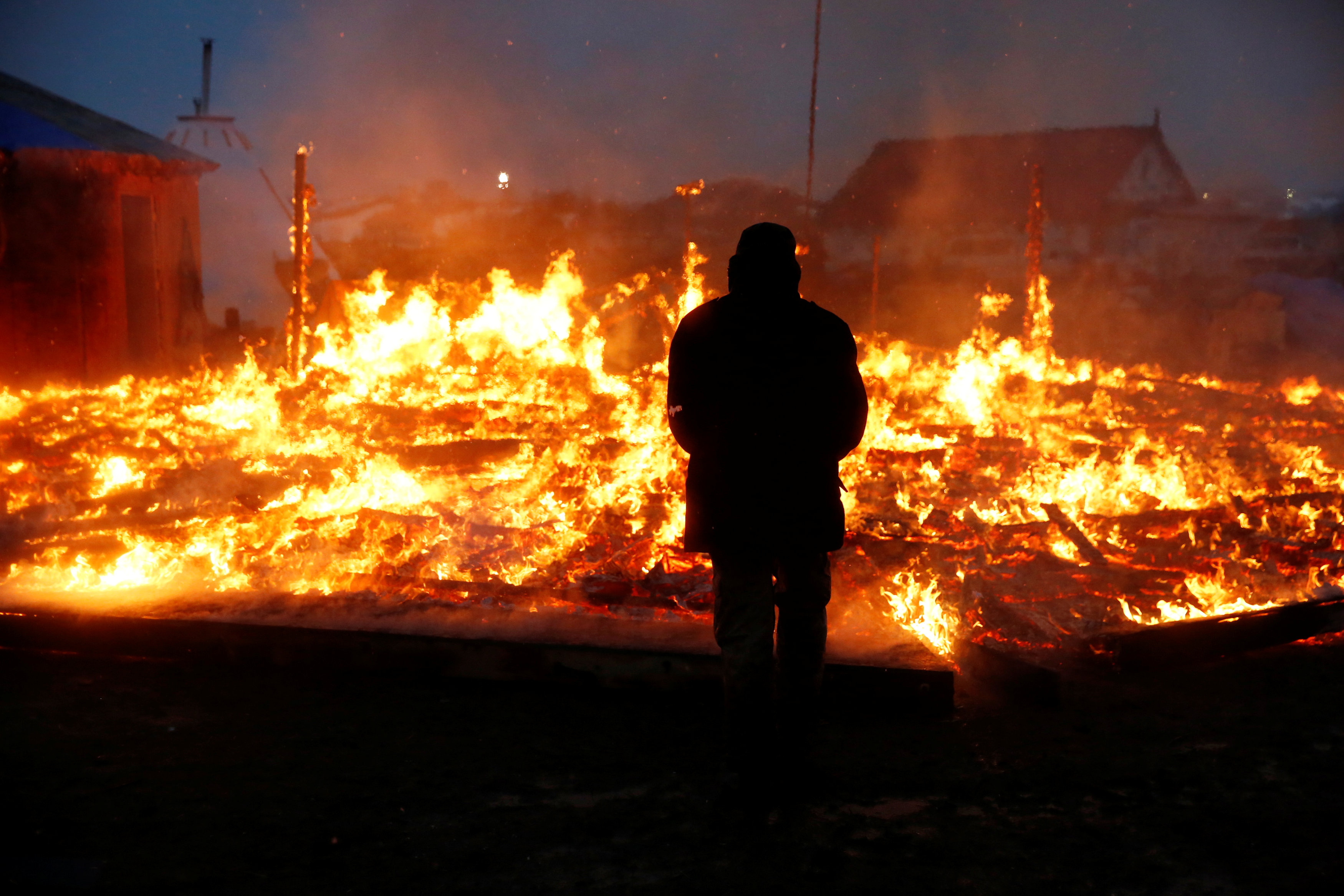 An opponent of the Dakota Access oil pipeline watches a building burn after it was set alight by protesters preparing to evacuate the main opposition camp against the pipeline near Cannon Ball, North Dakota, S, February 22, 2017. Credit: Terray Sylvester/Reuters