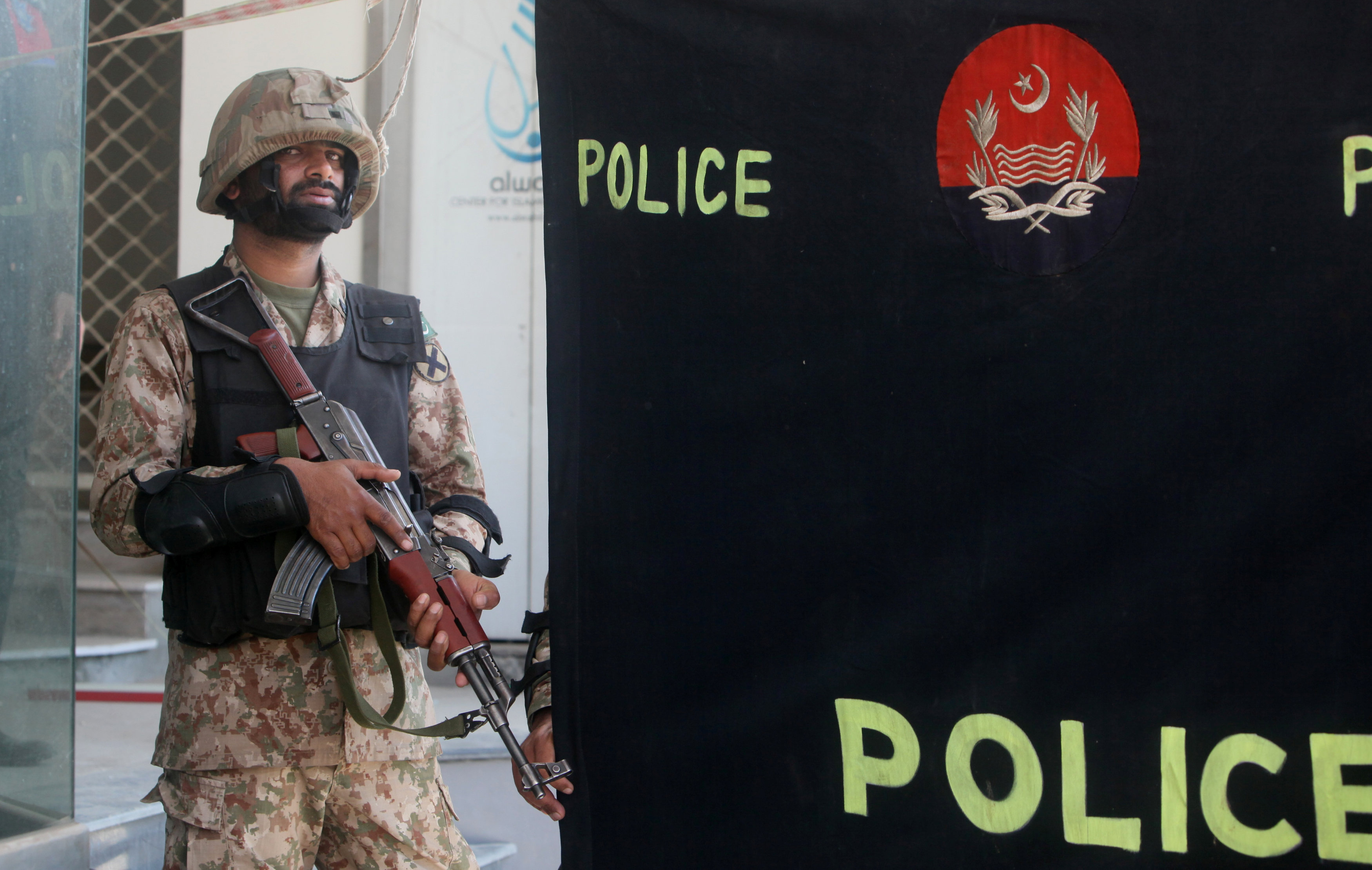 A soldier stands guard at the police screen as investigators collect evidence at the scene of a blast in a upscale neighborhood in Lahore, Pakistan February 23, 2017. Credit: REUTERS/Mohsin Raza