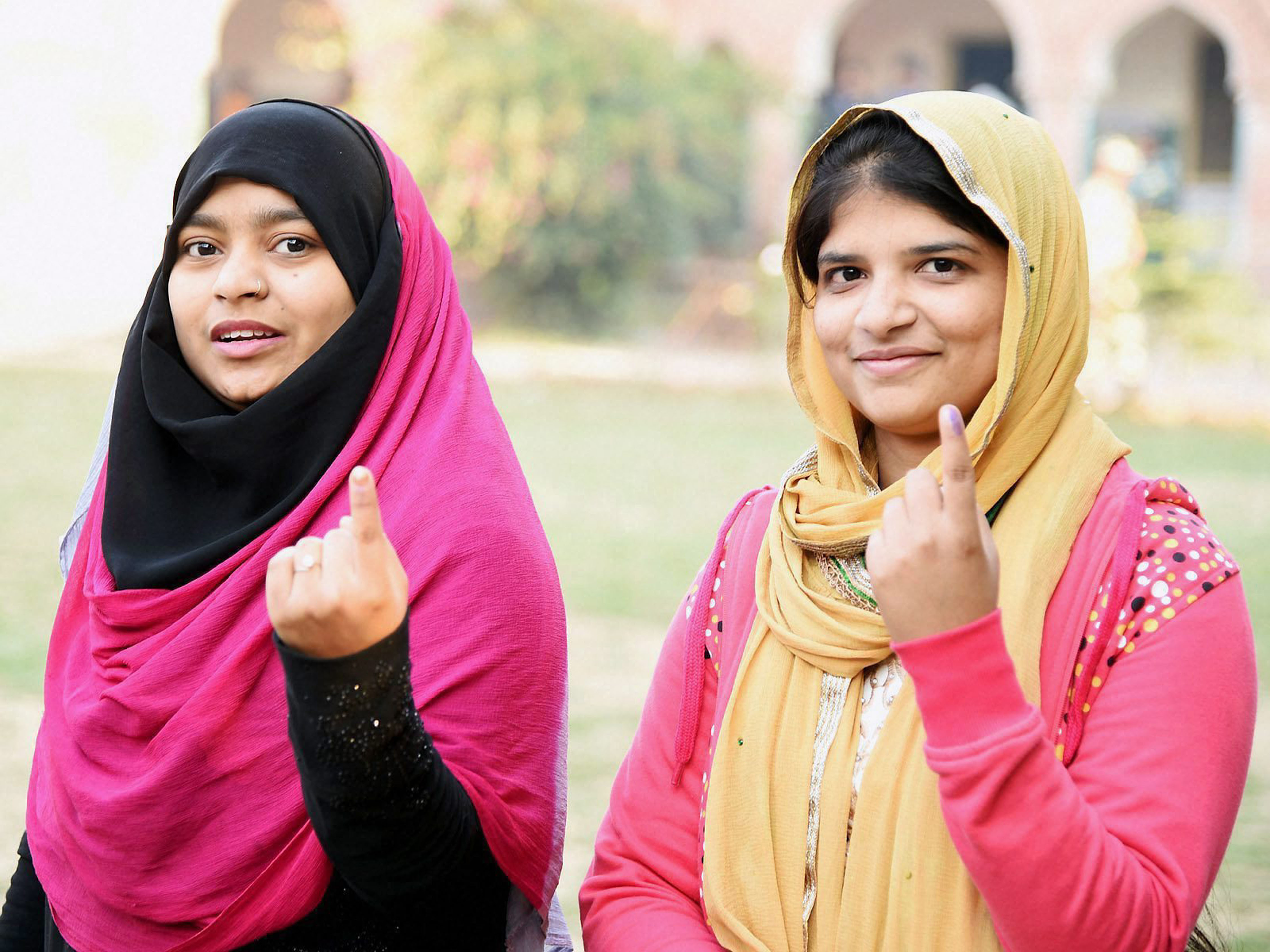 Aligarh: Muslim girls show their inked fingers after casting votes during the first phase of UP Assembly polls in Aligarh on Saturday. PTI Photo (PTI2_11_2017_000210B)