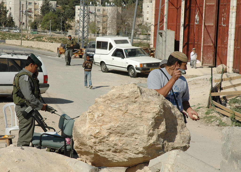 "Israeli settlers and guards in Hebron: The   site of an illegal occupation of a Palestinian house in Hebron. Note: the ""minder"" guards and the young Israeli settler at the front - taking pictures of the photographer - with stone in hand. Credit: Peter Mulligan/Flickr CC 2.0"