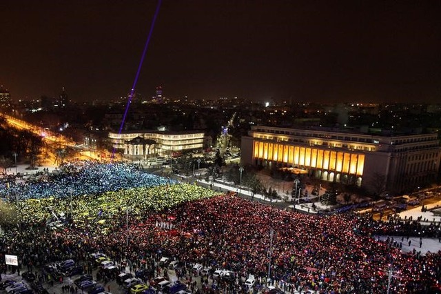 Protesters display the Romanian national flag colours during a demonstration in front of the government building in Bucharest, Romania, February 12, 2017. Credit: Reuters/Liviu Florin Albei