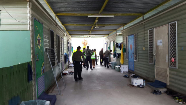 Authorities inside the Manus Island refugee camp in Papua New Guinea walk around the camp serving deportation notices to detainees, February 9, 2017. Credit: Reuters