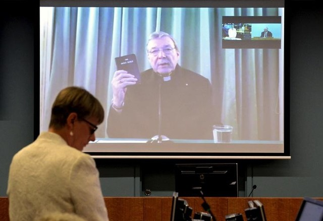 Senior Counsel Assisting Gail Furness stands in front of a screen displaying Australian Cardinal George Pell as he holds a bible while appearing via video link from a hotel in Rome, Italy to testify at the Australia's Royal Commission into Institutional Response to Child Sexual Abuse in Sydney, Australia, February 29, 2016. REUTERS/Jeremy Piper-Oculi/Handout via Reuters/Files