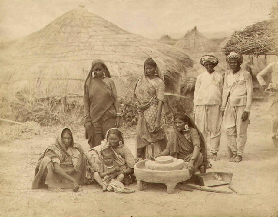 Bhil women grinding corn in a village. Credit: Wikimedia Commons