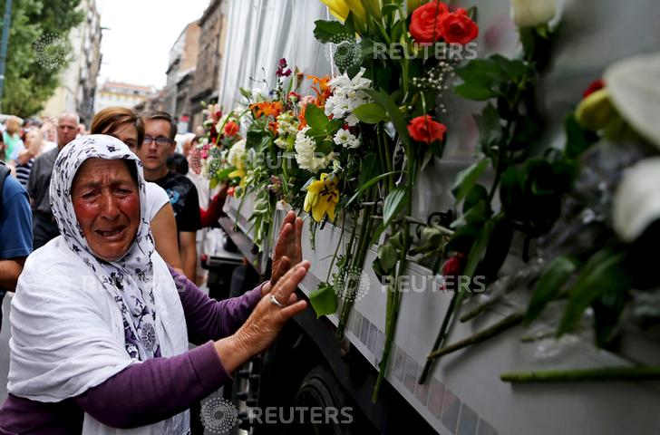 A woman cries beside a truck carrying 136 coffins of newly identified victims of the 1995 Srebrenica massacre, in front of the presidential building in Sarajevo July 9, 2015. Credit: Reuters