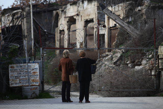 Two women stand in front of a gate in the UN-controlled buffer zone in Nicosia, Cyprus. Credit: Reuters