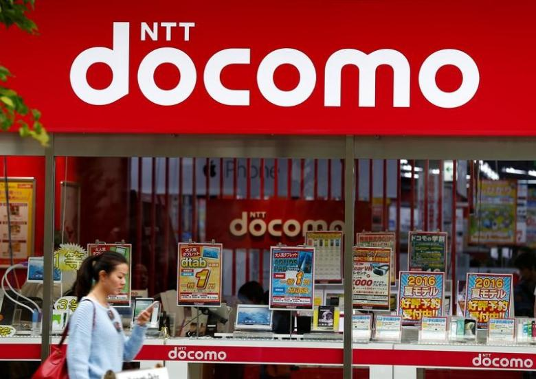A woman walks past a brach of Japanese mobile communications company NTT Docomo in Tokyo, Japan, May 16, 2016. Credit: Reuters/Thomas Peter