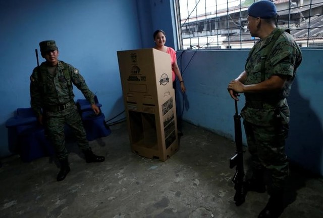 Soldiers stand guard as an election worker (C) prepares ballot boxes during the presidential election in a public school, used as a polling station, in Guayaquil, Ecuador February 19, 2017. Credit: Reuters