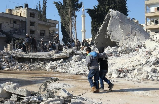 Boys walk at a site hit by airstrikes in the rebel-held city of Idlib, Syria February 7, 2017. Credit: Reuters