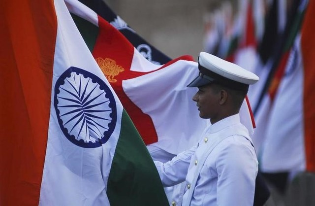 An Indian Navy soldier holds an Indian national flag during a dress rehearsal ahead of Navy Day celebrations in Mumbai, December 2, 2011. Picture taken on December 2, 2011. Credit: Reuters/Files