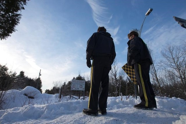 Royal Canadian Mounted Police (RCMP) officers stand on a hill looking over the US-Canada border into Hemmingford, Quebec, Canada February 14, 2017. Credit: Reuters